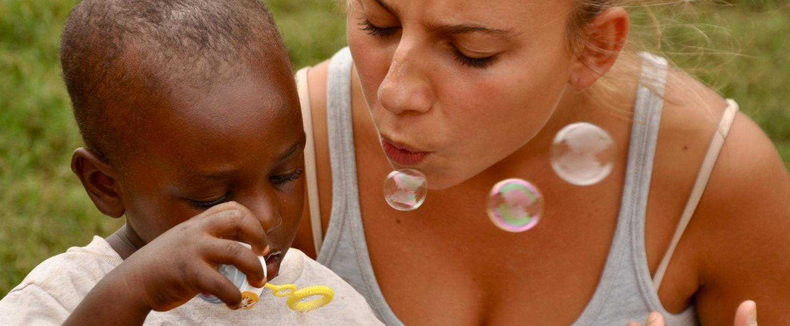 Childcare volunteer blows bubbles with a child in Ghana